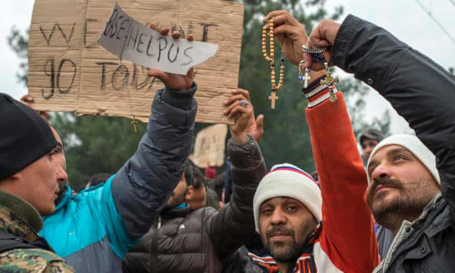 Refugees and migrants hold up Christian crosses and banners as they wait for permission to cross the border between Macedonia and Greece.