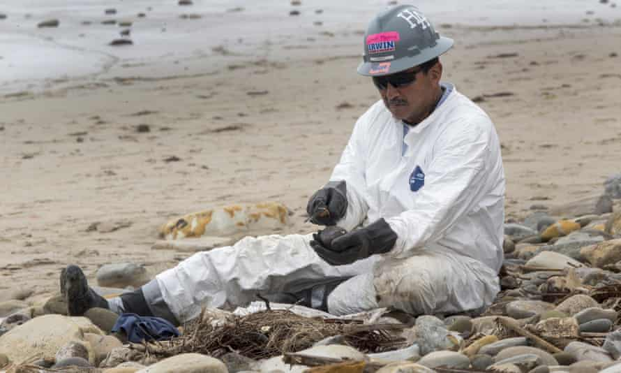 A worker cleans oil contamination one rock at a time in areas affected by an oil spill at Refugio state beach.