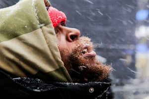 New York, NYA man looks at falling snow in Times Square as the cold weather front hits reaches Manhattan.