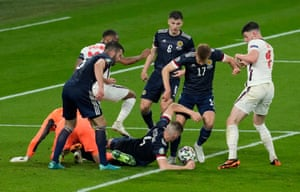 Scott McTominay and Stuart Armstrong of Scotland scramble to get rid of the ball with Declan Rice of England in pursuit.