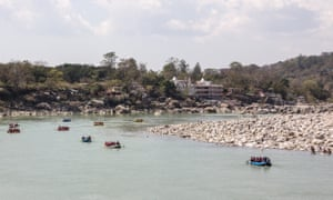Rafts and dinghies on the Ganges. They pass an ashram coming from the rapids of the Ganges at Rishikesh, India.
