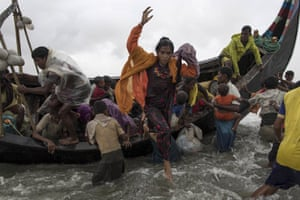 Rohingya refugees jump from a wooden boat as it begins to tip over after travelling from Myanmar