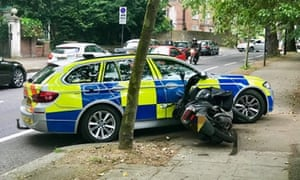 A moped stopped by a police car after a pursuit