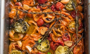 A tray of different coloured roast tomatoes with herb sprigs on top