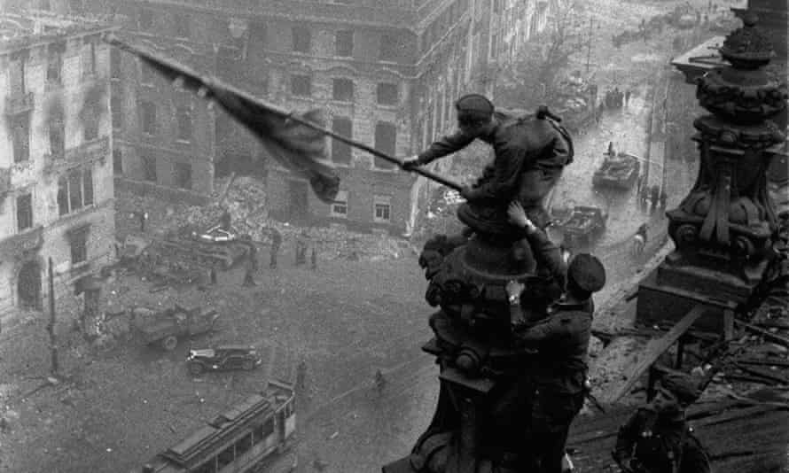 Soviet soldiers hoist the red flag over the Reichstag in May 1945. The Red Army committed mass rapes on the road to Berlin.