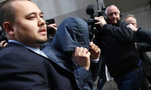 Mazher Mahmood covers his face with his coat as he leaves the Old Bailey on Wednesday.