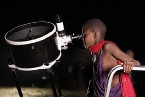 A Kenyan young boy looks through a telescope as the moon turns red in Oloika.