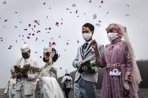 Couples sow flowers as they attend a mass wedding to commemorate the 75th Indonesia's National Independence Day at Cemara Sewu beach amid the coronavirus pandemic in Yogyakarta, Indonesia.