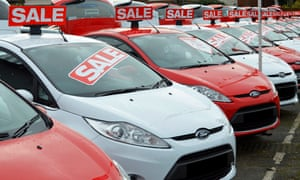 Sale of used Ford cars on dealership forecourt outside showroom arranged alternate red and white obscured numberplatesD2GRYJ Sale of used Ford cars on dealership forecourt outside showroom arranged alternate red and white obscured numberplates