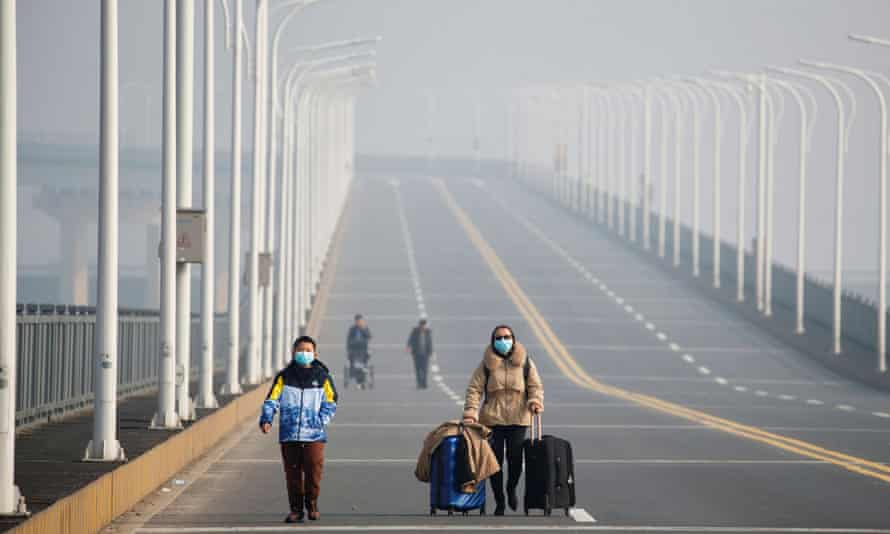 A mother and her son arrive from Hubei province at a checkpoint at the Jiujiang Yangtze River Bridge in Jiangxi province