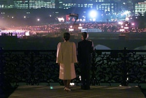 Emperor Akihito and Empress Michiko acknowledge cheering wellwishers waving lanterns as they make a public appearance on Nijubashi, or the Double Bridge, outside the Imperial Palace in Tokyo during the 10th anniversary celebrations of Akihito's accession to the throne in November 1999