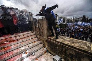A protester clashes with riot police in front of the Greek parliament in Athens