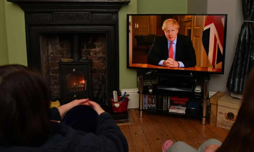 A family watch the prime minister's address on Monday evening.