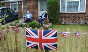 Old people in a garden with union jacks