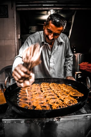 A man stands over a large pan making a traditional sweet called jalaibi.