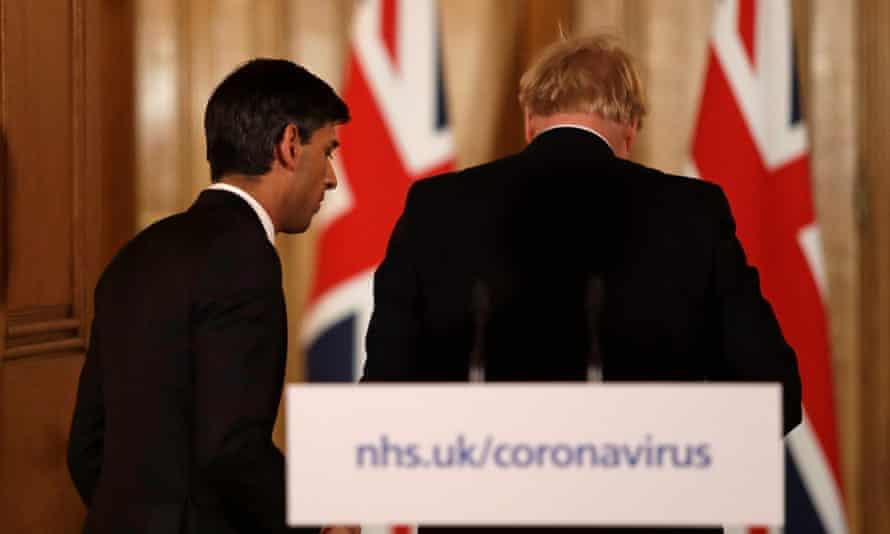 The chancellor, Rishi Sunak, leaves the coronavirus press conference with Boris Johnson.
