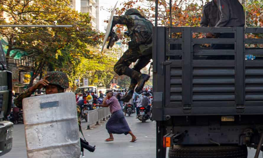 A man runs as soldiers jump down from a vehicle during a clash with protesters demonstrating against the military coup
