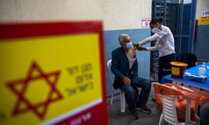 A Palestinian laborer who works in Israel receives his first dose of the Moderna Covid-19 vaccine at a checkpoint crossing between Israel and the West Bank.