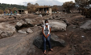 Eufemia Garcia sits on a rock on top what used to be her family house in San Miguel Los Lotes.
