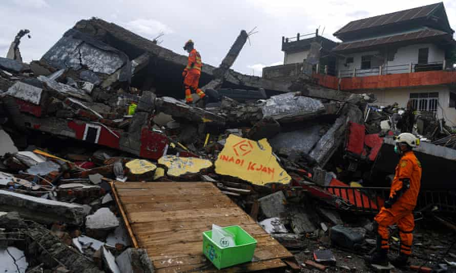 Search and rescue personnel inspect a collapsed building in Mamuju on Saturday.