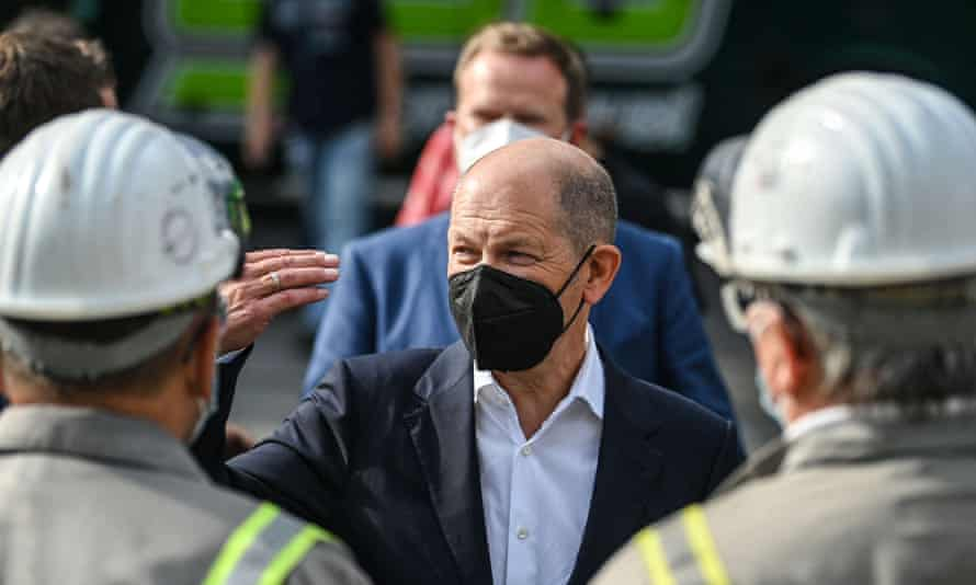 A masked Olaf Scholz talks to employees in safety gear