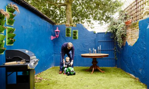 The small garden with high blue walls, and a toddler in a car being pushed by Will on the grass