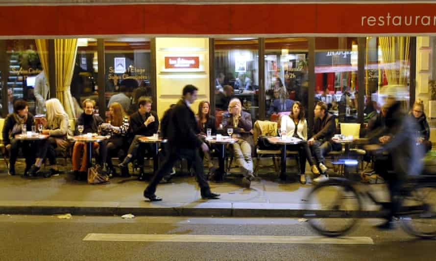 A man walks on the street as people sit at a table outside a bistro in Paris, France.