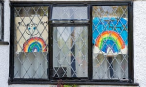 Colourful 'Thank You NHS' children's rainbow drawings in house windows in Slough.