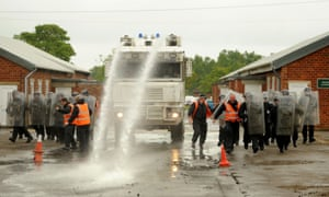 Police officers training with a water cannon