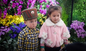 Two children pose in front of a display at the exhibition of Kimilsungia and Kimjongilia flowers -- named for North Korea's former leaders -- in Pyongyang, North Korea.