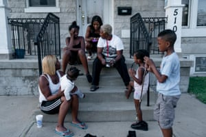 Chante Bass, top right, hangs out on her front porch with her family in St Louis on Thursday, Sept. 12, 2019. The family lives in north St Louis, which has long been plagued by gun violence. At least 13 children have died of gunshot wounds in St Louis city this year, and six children in St Louis County have been killed by gunfire.