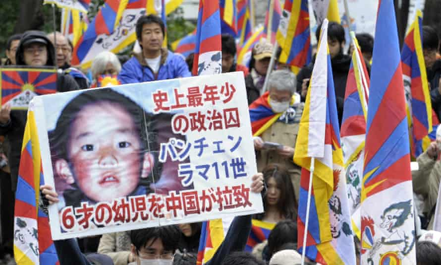 A protester holds a placard with portrait of Dalai Lama's choice for Panchen Lama, Gedhun Choekyi Nyima.