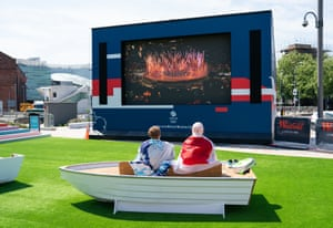 Big-screen viewers sitting on speedboat-shaped chair
