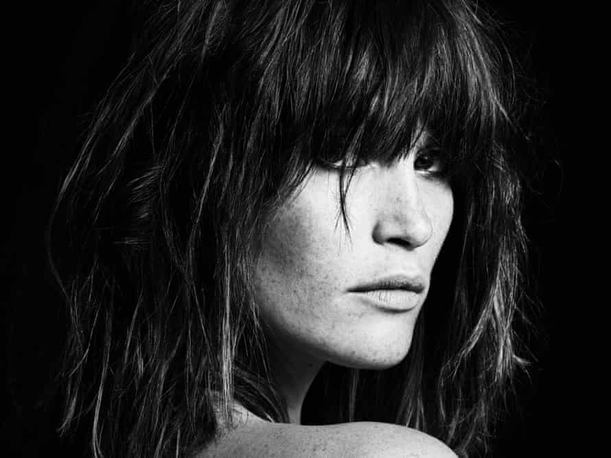 Gemma Arterton in profile looking over a bare shoulder, with dark, straightened hair: in black and white