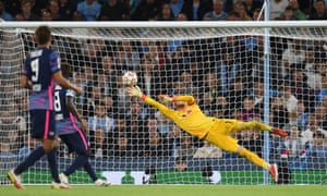 RB Leipzig's goalkeeper Peter Gulacsi dives in vain to save a shot from Manchester City's Portuguese defender Joao Cancelo.