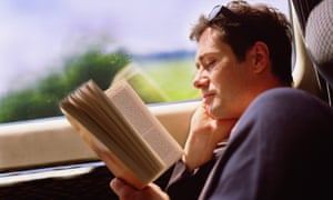 Man reading paperback book on train