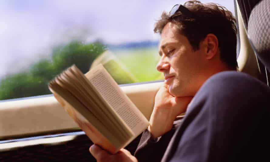 Man reading paperback book on train