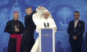 An aide adjusts Pope Francis' cape as he speaks at the Knock shrine