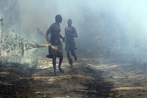 Men run out of a field in South Sudan after setting it on fire