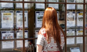 A young woman looks into the window of an estate agent.