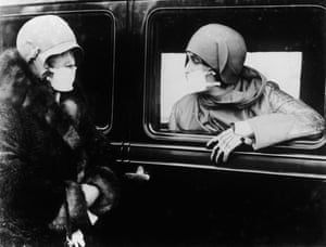 Two women wearing masks taped over their mouths chat on the street in 1918.
