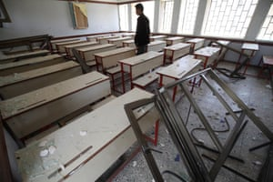 On 28 April, the son of the guard at Ibn Sina School walks through rows of desks while checking a damaged classroom in the facility, in Yemen's capital, Sana''a