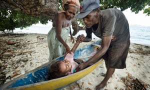 A couple place a small child in a canoe