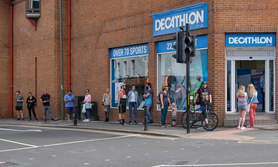 Customers queue outside a shop in Guildford, Surrey, after it reopened during the coronavirus crisis.