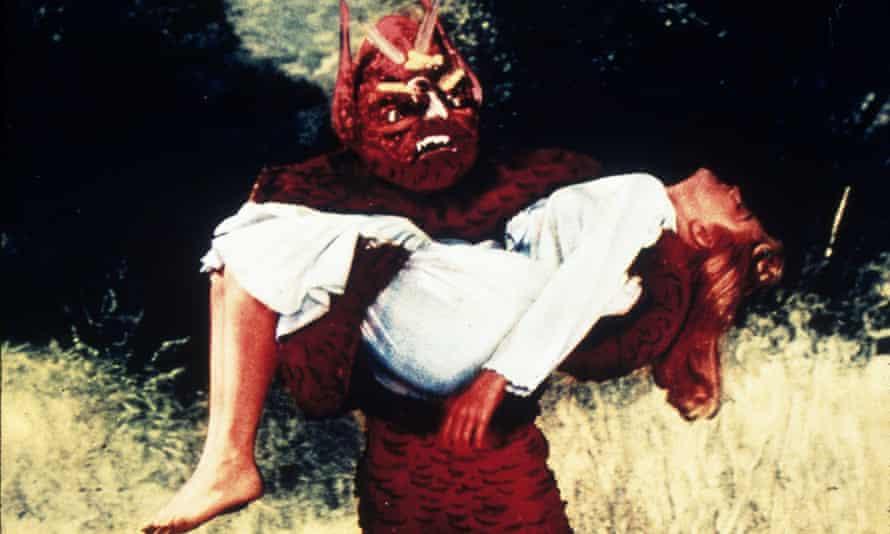 A film still of an alien carrying a sleeping woman