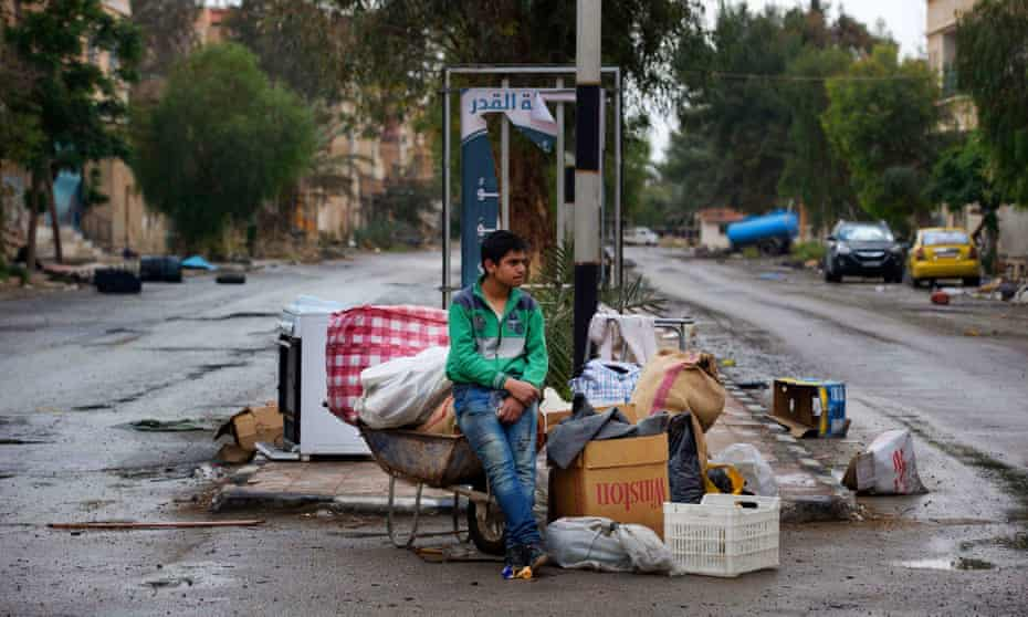 A boy waits to load his family's belongings on to a bus in Palmyra, Syria.