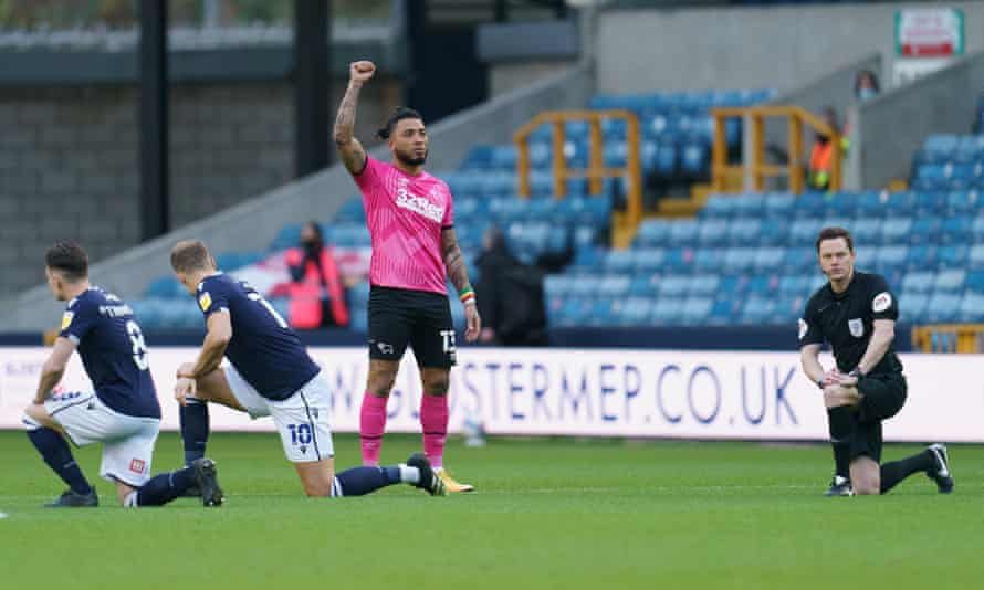 Derby's Colin Kazim-Richards stands with a fist raised as Millwall fans boo players for taking a knee this month.