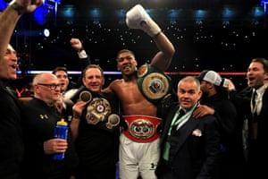 Joshua celebrates victory with his team, now the IBF, WBA and IBO heavyweight world champion.