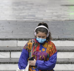 A woman wears a mask for protection against Covid-19 while going into a subway station in Bucharest.