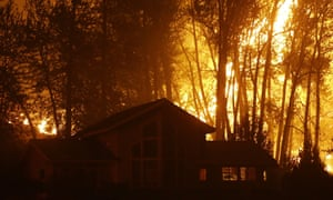 A wildfire burns behind a home in Twisp, Washington, in August 2015.